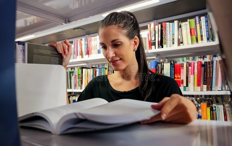Lecture d'étudiante dans la bibliothèque de campus d'université photo libre de droits