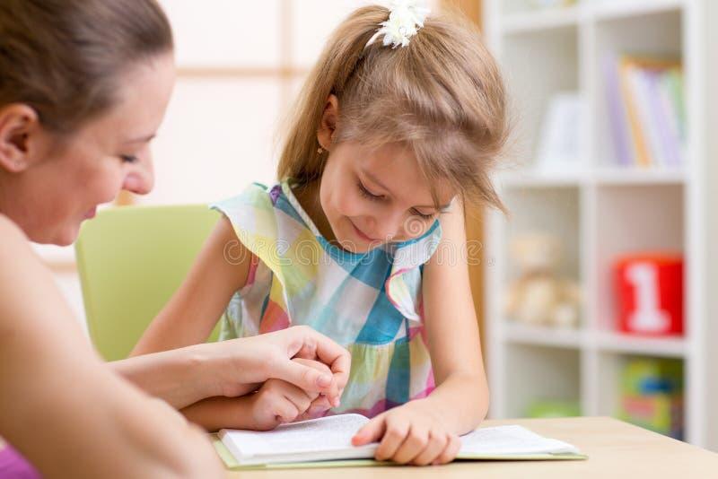 Lecture d'enfant d'élève du cours préparatoire avec la mère dans la crèche photo stock