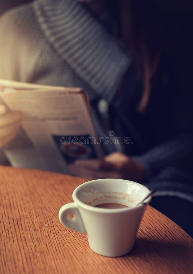 Lecture d'un journal avec du caf? photo libre de droits
