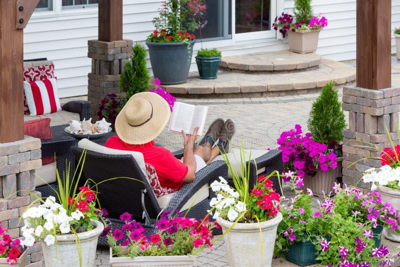 Lecture de détente d'homme sur un patio extérieur photos stock