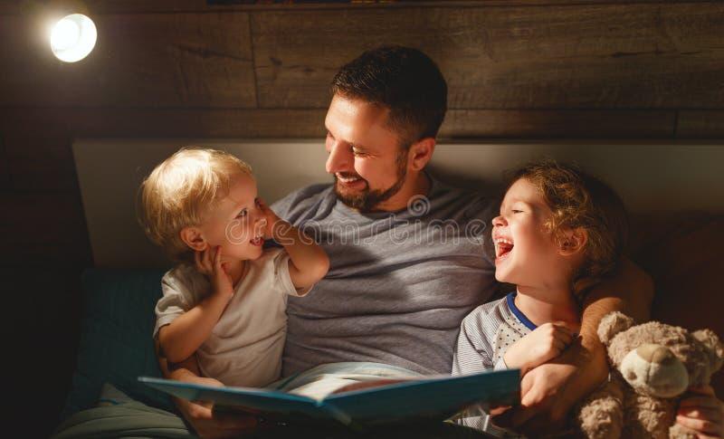 Lecture de famille de soirée le père lit des enfants livre avant goin images stock