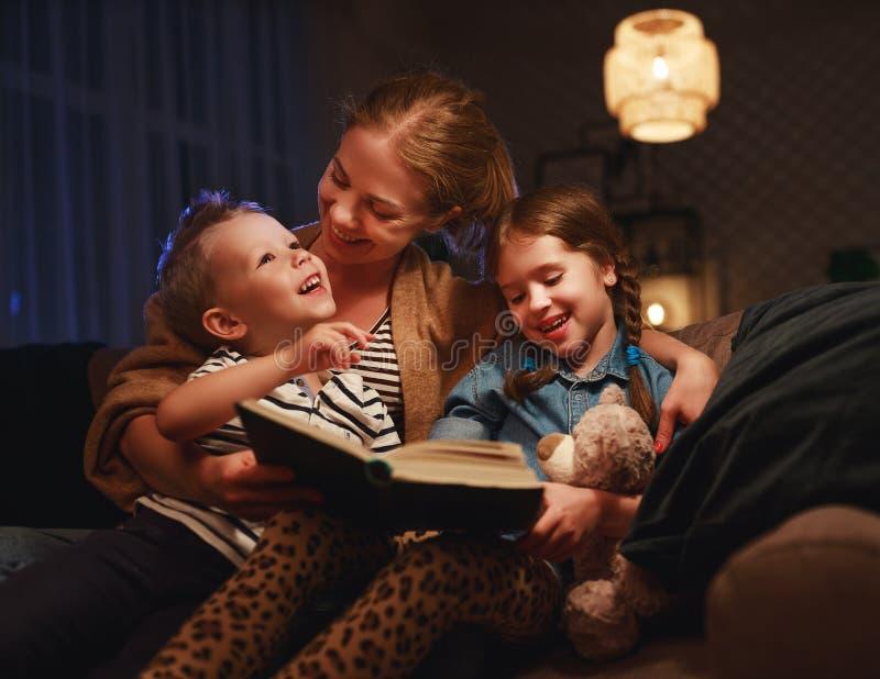 Lecture de famille de soir?e la mère lit des enfants livre avant d'aller au lit image stock