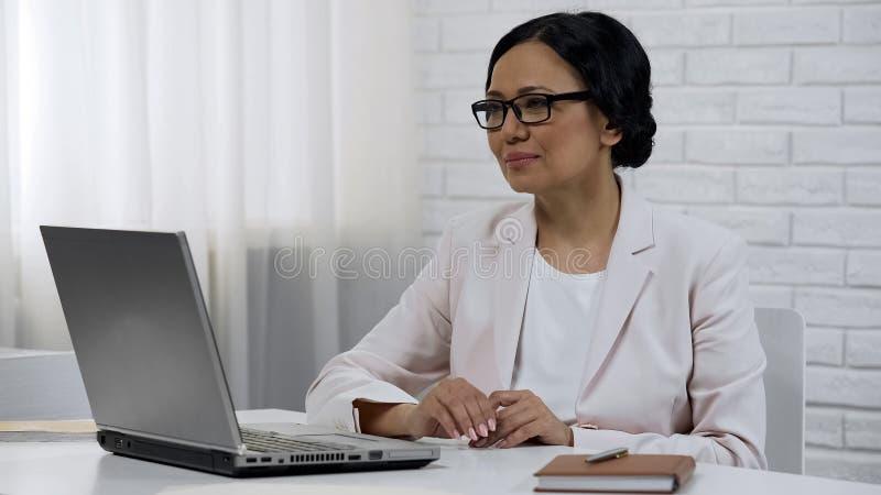 Lecture de femme d'affaires sur des états de contrat d'ordinateur portable, se reposant dans l'armoire privée photos stock