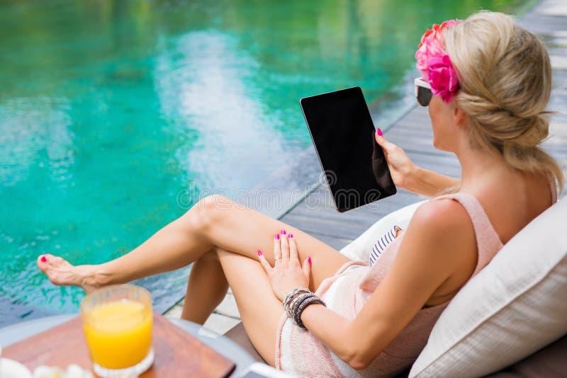 Lecture de femme quelque chose sur la tablette par la piscine photo libre de droits