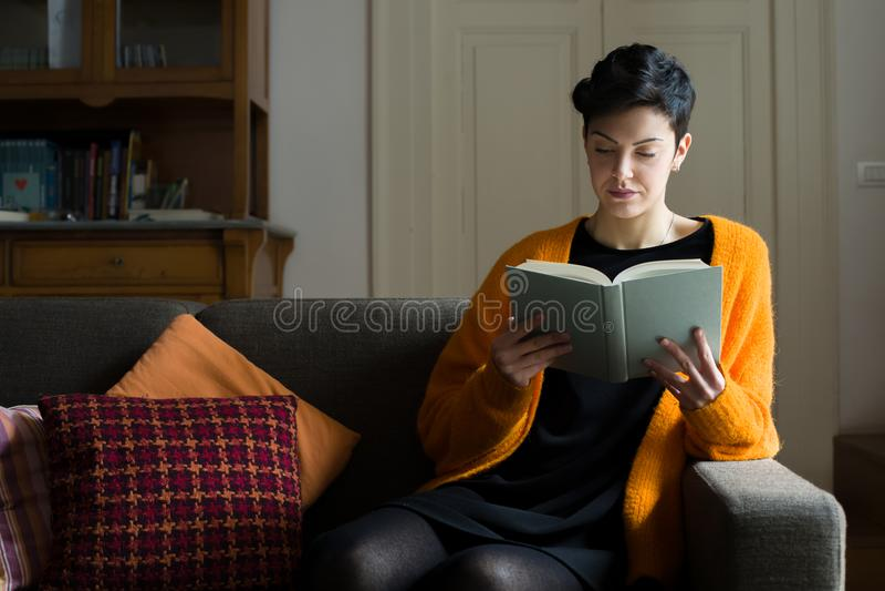 Lecture de femme sur un sofa photo libre de droits