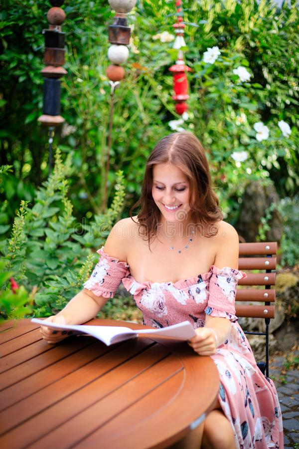 Lecture de jeune femme dans une magazine vide tout en se reposant dans l'orphie photographie stock