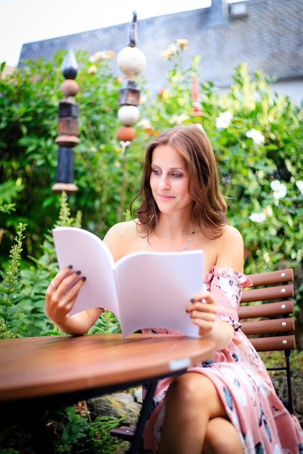 Lecture de jeune femme dans une magazine vide tout en se reposant dans l'orphie photo stock