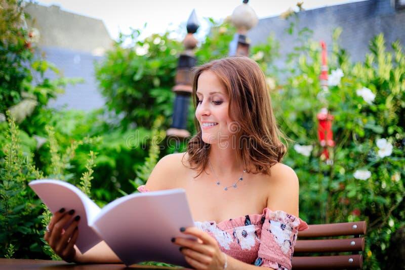 Lecture de jeune femme dans une magazine vide tout en se reposant dans l'orphie photos stock