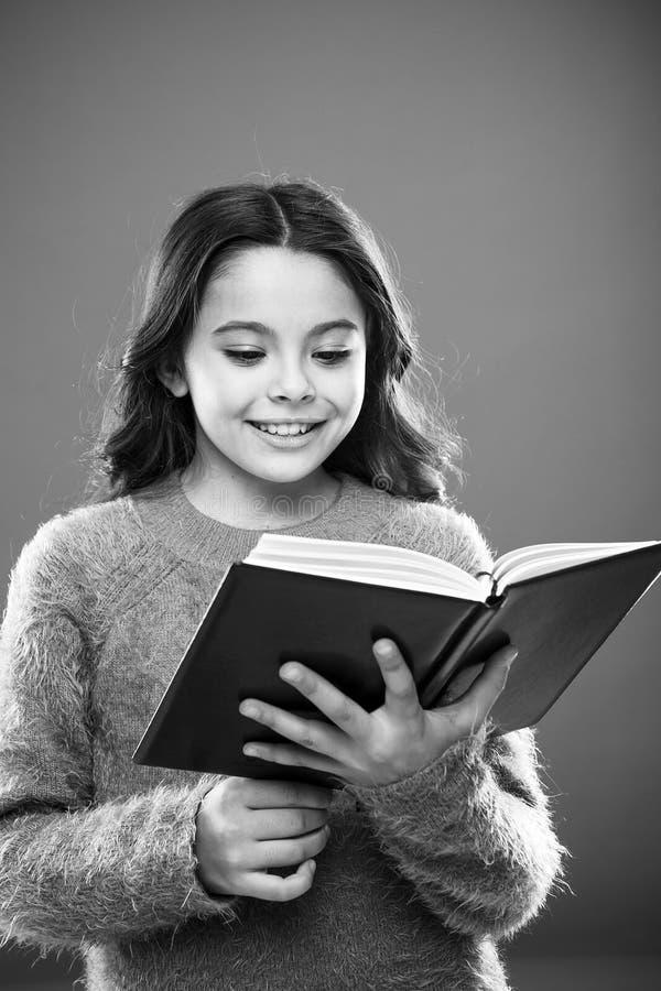 Lecture de la pratique pour des enfants Le livre de prise de fille a lu l'histoire au-dessus du fond orange L'enfant apprécient l image stock