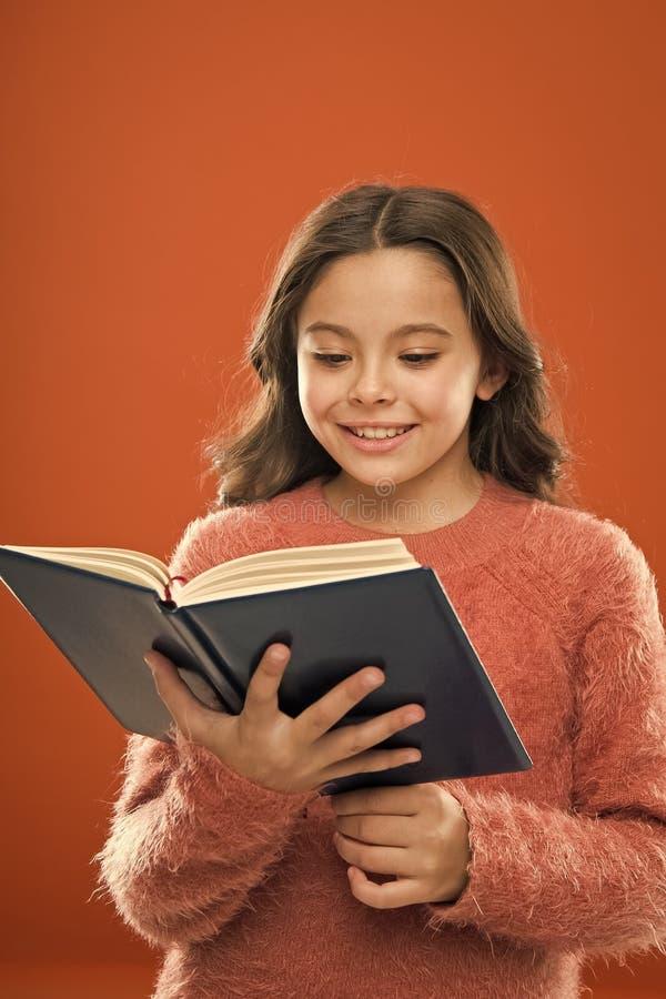 Lecture de la pratique pour des enfants Le livre de prise de fille a lu l'histoire au-dessus du fond orange L'enfant appr?cient l photographie stock libre de droits