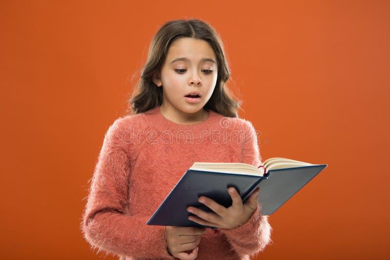 Lecture de la pratique pour des enfants La littérature d'enfants Le livre de prise de fille a lu l'histoire au-dessus du fond ora photographie stock libre de droits