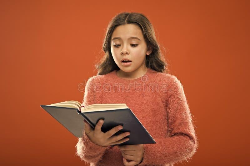 Lecture de la pratique pour des enfants La litt?rature d'enfants Le livre de prise de fille a lu l'histoire au-dessus du fond ora photographie stock