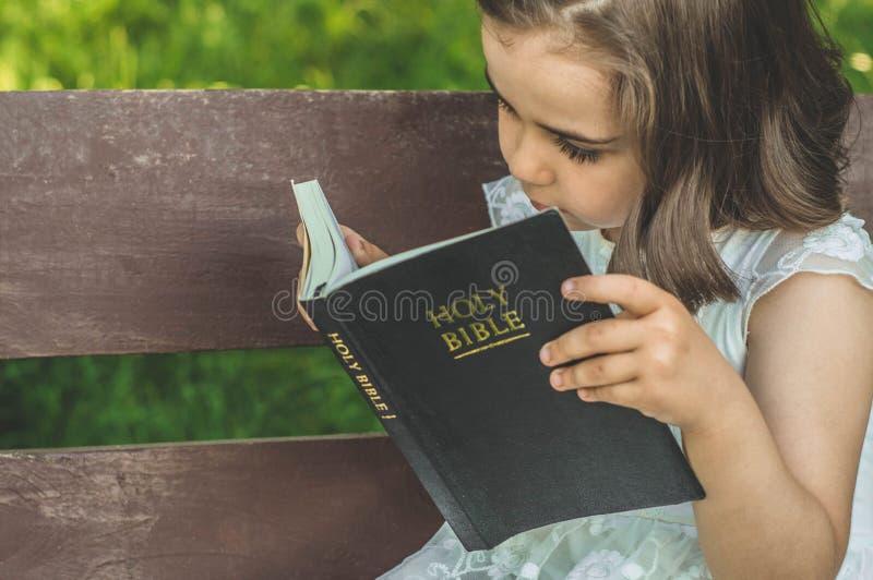 Lecture de la Sainte Bible dans l'extérieur La fille chrétienne tient la bible dans des ses mains se reposant sur un banc photo stock