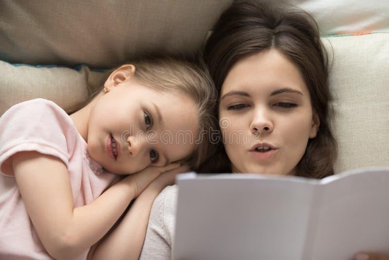 Lecture de mère à peu de conte de fées de fille avant lit photo stock