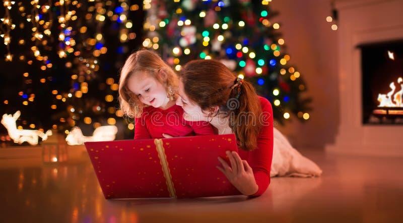 Lecture de mère et de fille à l'endroit du feu le réveillon de Noël image libre de droits