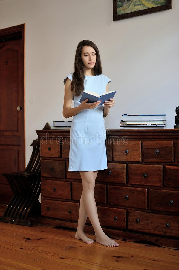 Lecture debout de jeune femme un livre images stock