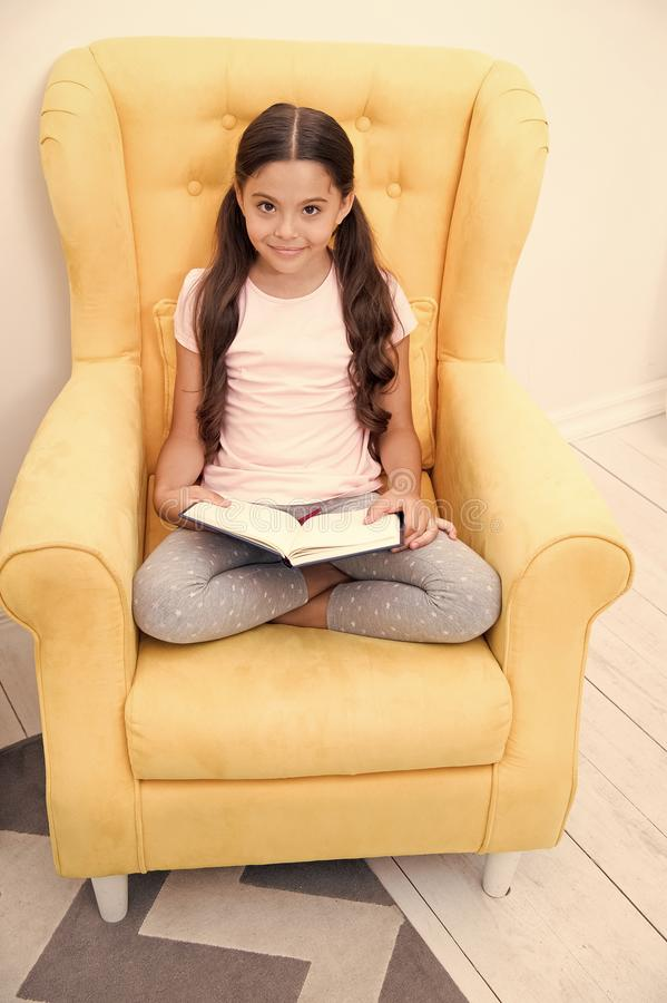 Lecture du passe-temps utile L'enfant de fille reposent le livre lu par fauteuil jaune Rat de bibliothèque mignon d'enfant Temps  photographie stock