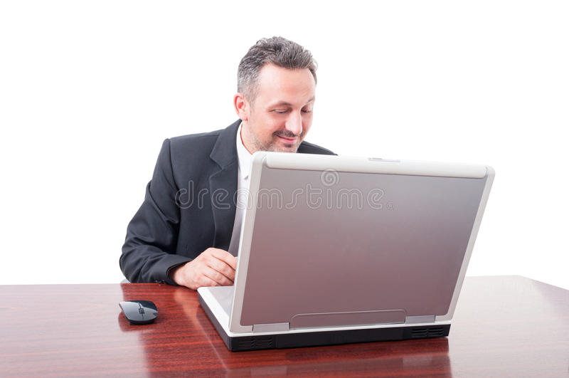 Lecture exécutive heureuse de directeur quelque chose sur l'ordinateur portable images stock