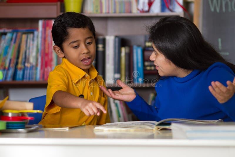 Lecture hispanique d'enfant avec la mère images stock