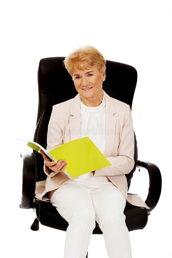 Lecture pluse âgé de femme d'affaires de sourire notes photo stock