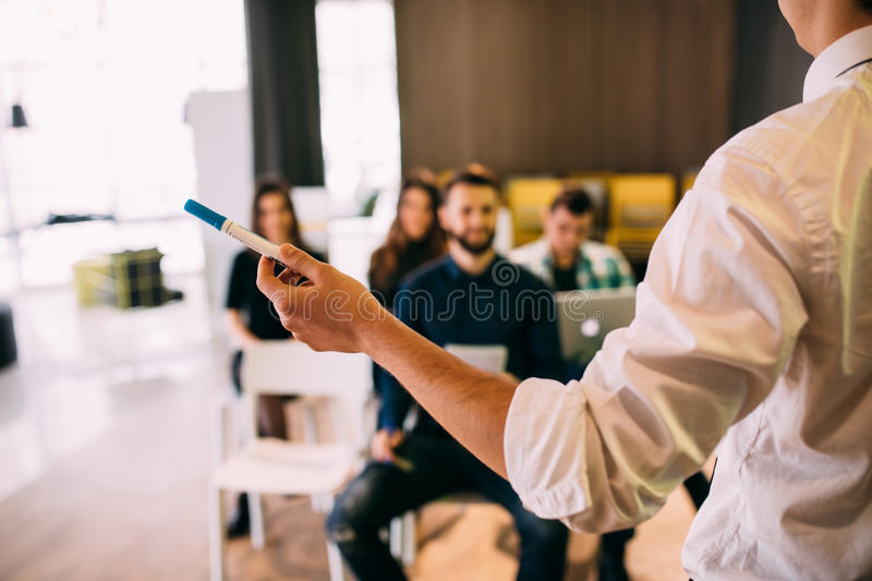 Lecture and training in business office for white collar colleagues. Focus on hands of speaker. stock photos