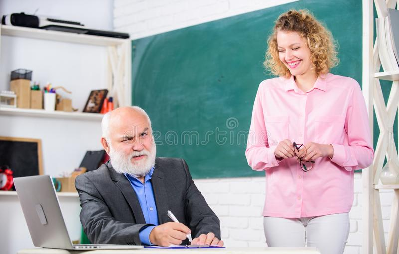 Lecturer educator helping student with test. Man mature school teacher and girl with laptop. Difficult tasks. Pass exam stock image
