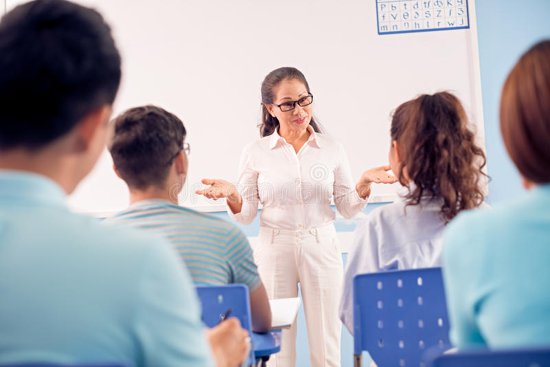 Lecturer. Image of a mature lecturer gesturing while explaining something to the students in the classroom on the foreground royalty free stock photos