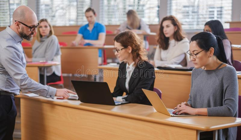 Lecturer and multinational group of students in an auditorium stock photos