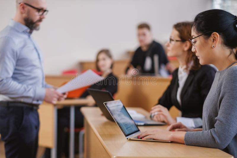 Lecturer and multinational group of students in an auditorium royalty free stock photo