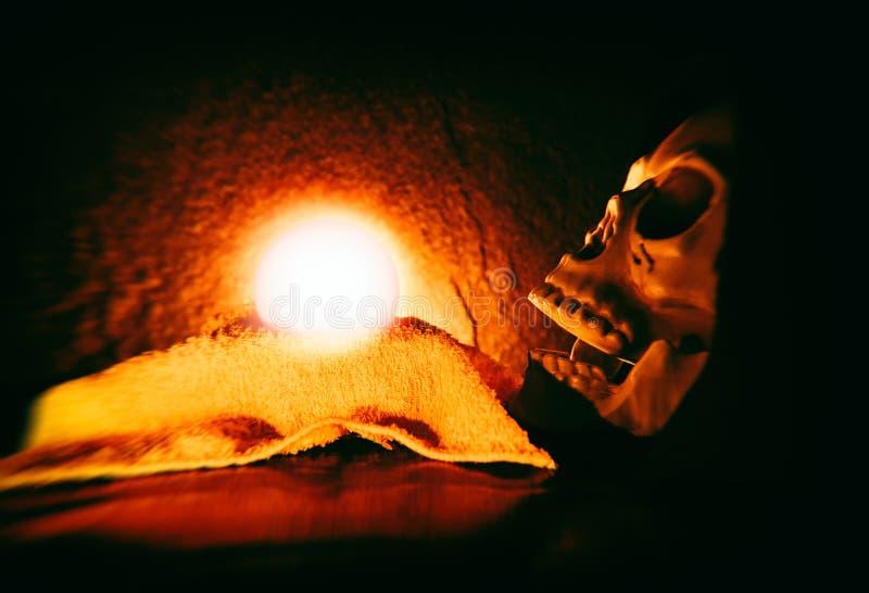 Lectures et voyance de voyant avec le crâne humain et les prévisions magiques de boule s'allumant sur le fond foncé image stock