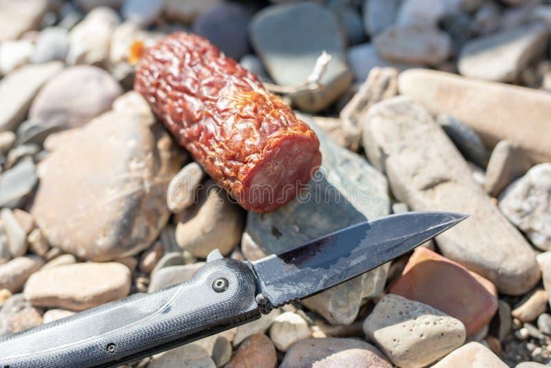 Lecząca kiełbasa i łowieckiego noża lying on the beach na kamieniach zdjęcia stock
