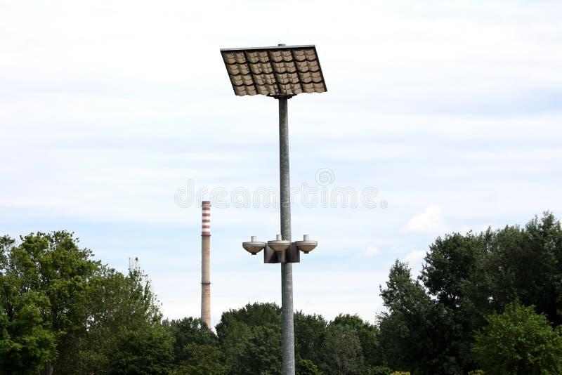 LED现代路灯到底反射器指向往大反射性盘区登上在与工业的强的金属杆顶部 免版税库存照片
