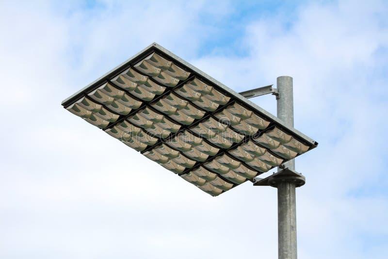 LED路灯到底反射器的大反射性盘区登上在强的金属杆顶部 库存照片