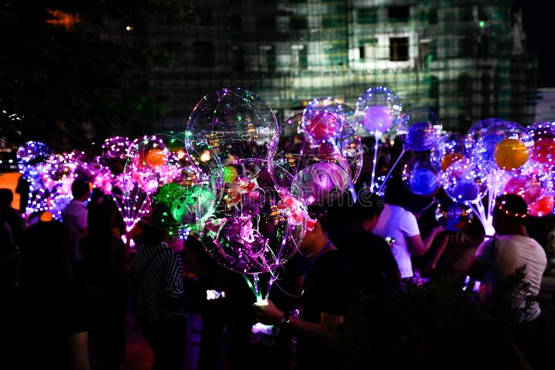 LED balloons people, holding many lighted balloons filled with toys and lights royalty free stock photo