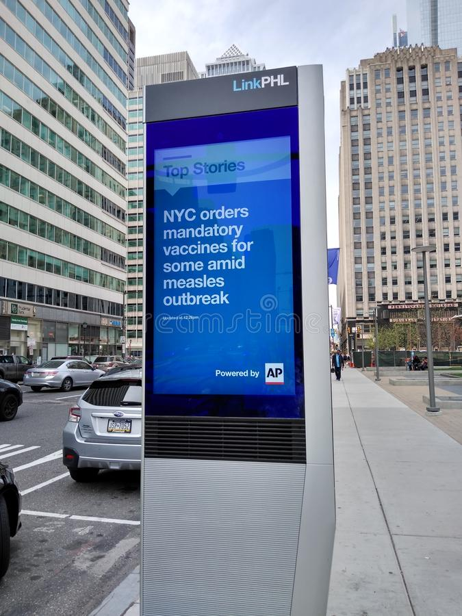 Measles, NYC Mandatory Vaccines, Measles Outbreak. This LED billboard in Philadelphia highlights top stories from around the world, including the latest on the royalty free stock photo