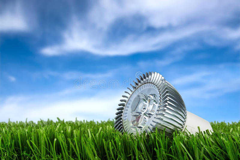 LED bulb. Led buld on grass in front of blue sky