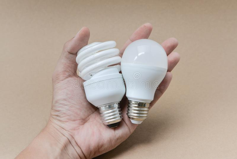 LED bulb and Fluorescent bulb on hand stock image