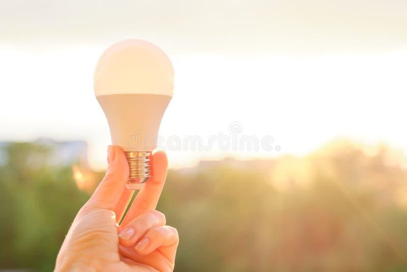 Led bulb, hand holding lamp, evening sunset sky background.  stock images
