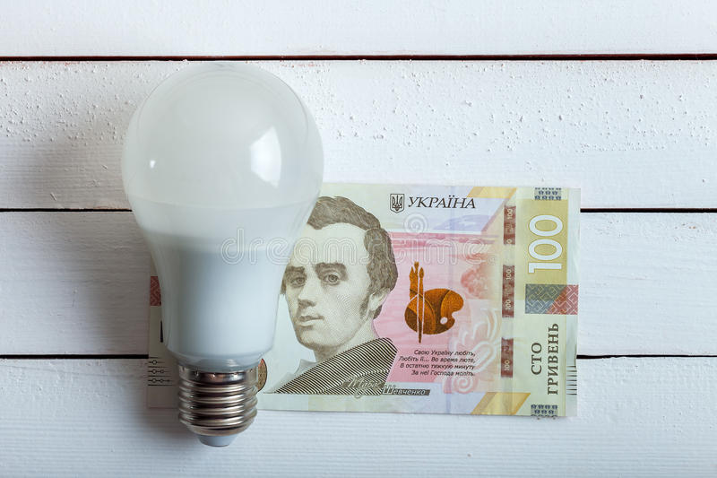 Led bulb with money on table. royalty free stock photos