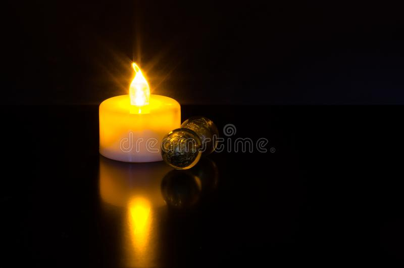 Led candle light with sparkly reflection and green marble balls on black background royalty free stock photos
