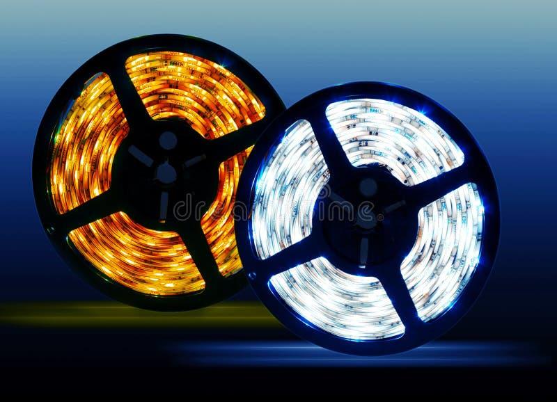 Led diode shining coils on blue background. Led strip coil closeup. Diode shining rope on blue background royalty free stock images