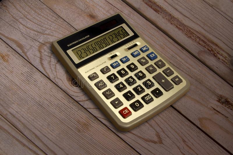 LED display electronic calculator on wooden background. Battery powered calculator stock images