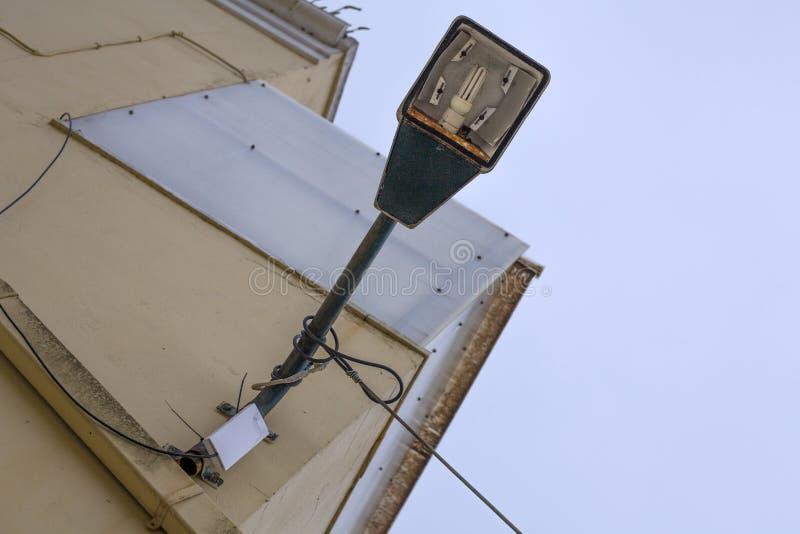 LED fixade på till en krökninglampstolpe framme av en byggnad Lampstolpen klämmas fast på den rosa väggen med trådarna roped runt royaltyfri foto