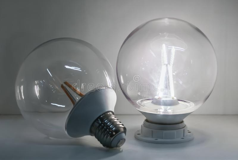 A led glass transparent lamp classic ball form is on and a led glass transparent lamp with an orange leds is off on white. A led glass transparent lamp classic royalty free stock photography