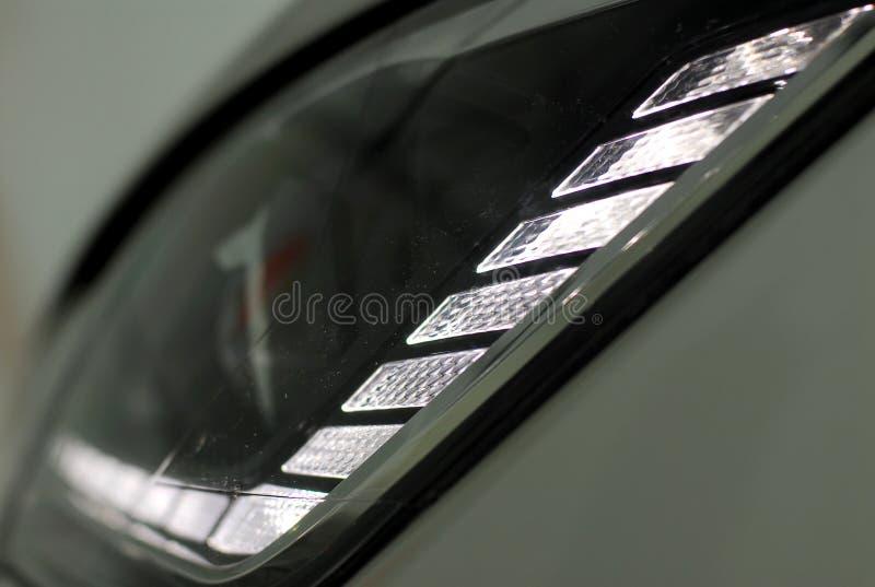 LED headlamp. LED Headlight detail of a white modern car royalty free stock image