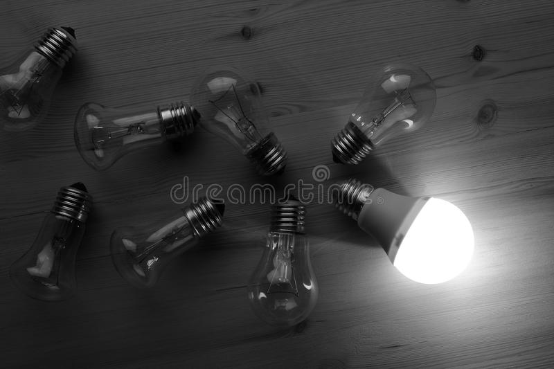 LED and incandescent lamps. Glowing LED lamp including incandescent lamps on a wooden table stock images