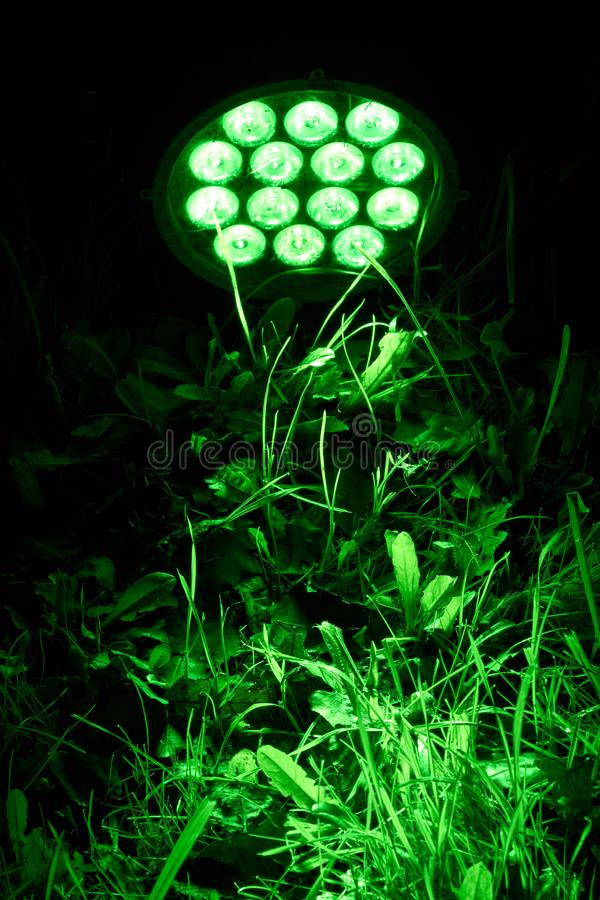 LED lamp. A bright green LED lamp lights up a meadow stock photo