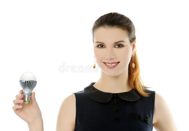 LED lamp. Cheerful girl holding LED lamp stock photos