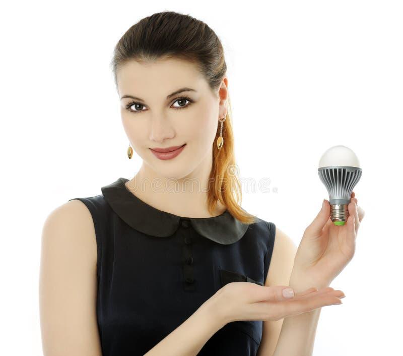 LED lamp. Cheerful girl holding LED lamp stock image
