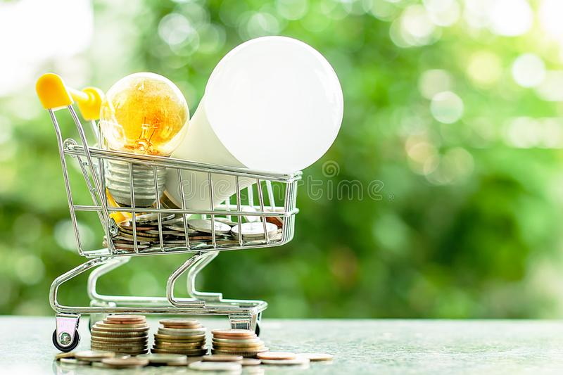 Led lamp and glowing light bulb in mini shopping cart or trolley. With money coins against blurred natural green background for finance, saving energy and royalty free stock image